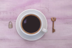 Closeup picture of cup of coffee with lock and key Stock Image