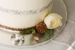 Closeup picture about a detail of white wedding cake with ornaments, with white gold wedding bands royalty free stock image