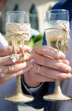 Closeup picture of hands holding glasses with champagne. Closeup picture of hands of the newlyweds holding a beautifully decorated wedding glasses with champagne Royalty Free Stock Photo