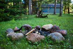 Campfire pit on green lawn with a hammock hanging in the background - 2/2 royalty free stock image
