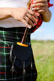 Closeup picture of male playing bagpipe on green Royalty Free Stock Image