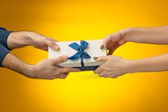 The closeup picture of man and woman`s hands with gift box Royalty Free Stock Photography