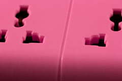 Closeup picture of a pink outlet isolated on black. Stock Images