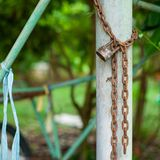 Closeup picture of rusted lock and chain on the steel column with blurred bokeh background. Love and commitment concept.  stock photos