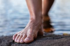 Young woman walking out of the water bare feet on a rock stock photography