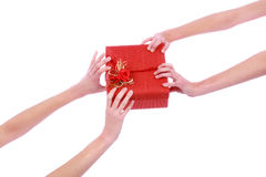 Closeup picture of two woman's hands with red gift box Royalty Free Stock Photography