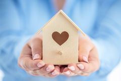 Closeup picture of woman hands holding small wooden house Royalty Free Stock Photo