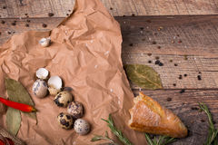 Closeup of a piece of a baguette, quail eggs with speckles, hot red chili pepper, grocery paper on a wooden background. Stock Photo