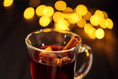 Closeup piece of glass of mulled wine with orange and cinnamon on dark black background, Christmas lights, l royalty free stock image