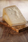 Closeup of piece of italian parmesan cheese on wooden cutting board Stock Image