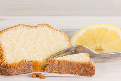 Closeup of a piece of lemon cake with a fork and lemon fruit Royalty Free Stock Photo