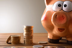 Closeup piggy bank with coins on wood table Stock Photo