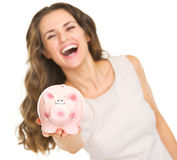 Closeup on piggy bank in hand of smiling woman Stock Photo