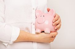 Closeup of a Piggy Bank in the Hands of a Woman Stock Photography