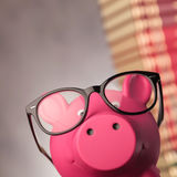 Closeup of a piggy bank wearing glasses near books Stock Images
