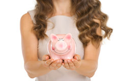 Closeup on piggy bank in woman hands Stock Images