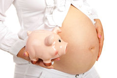 Closeup of piggybank and pregnant tummy Stock Images