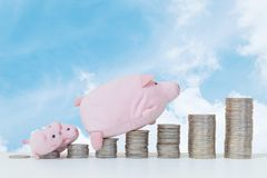 Closeup pile of coin start from low to high with pig doll and three little pig walk to the top of coin on with wood desk and blue. Closeup pile of coin start Royalty Free Stock Images