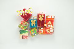Closeup pile of gift boxes wrapped by colourful paper for Christmas festival with isolated background. Selective focus of presents in beautiful package for stock images
