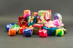 Closeup pile of gift boxes wrapped by colourful paper. For Christmas festival with isolated black background. Selective focus of presents in beautiful package royalty free stock photography