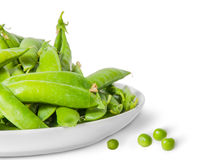 Closeup pile of green peas in pods in white plate. Isolated on white background Royalty Free Stock Photography