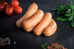 Closeup pile of raw short sausages with rucola and tomatoes. Closeup pile of raw short thick sausages with pink salt, spices, green rucola and tomatoes cherry on royalty free stock photography