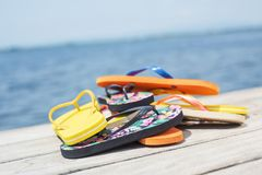 Flip-flops on a pier. Closeup of a pile of some different pairs of colorful flip-flops on a wooden pier next to the water stock image