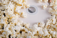 Closeup pile of white fluffy popcorn with dvd disc in the middle Royalty Free Stock Photography