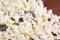 Closeup pile of white fluffy popcorn with tv remote control in the middle Stock Image