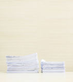 Closeup pile of work paper on blurred wooden desk and wall textured background in the meeting room under window light , hard work. Pile of work paper on blurred Royalty Free Stock Image