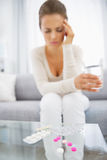 Closeup on pills and feeling bad young woman in background. Closeup on pills and feeling bad young woman  in living room in background Royalty Free Stock Images