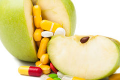 Closeup of pills and green apple Royalty Free Stock Photos