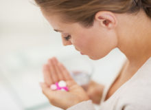 Closeup on pills in hand of young woman Stock Photos