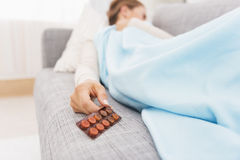 Closeup on pills pack in hand of ill young woman laying on sofa Stock Image