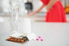 Closeup on pills on table and feeling bad girl in background Stock Photography