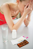 Closeup on pills on table and feeling bad girl in background Royalty Free Stock Photography