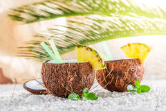 Closeup of pinacolada in coconut on sandy beach Stock Images