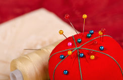Closeup of pin cushion. Closeup of pincushion with quilting fabrics and thread on the background Royalty Free Stock Photo