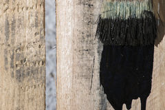 Closeup Of Pine Plank Being Painted In Black Color stock photography