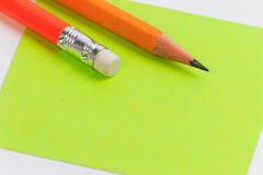 Closeup pink and green paper note with wood pencil. Royalty Free Stock Image