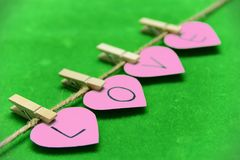 Closeup pink hearts with the word love on to the grass green moist. Closeup pink hearts with the word love being with clamping the wood clamp.Hanging on to the Royalty Free Stock Image