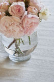Closeup of pink roses in vase on white tablecloth Stock Photos
