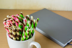 Closeup pink stripe wafer rolls on cup and diary. Royalty Free Stock Photography