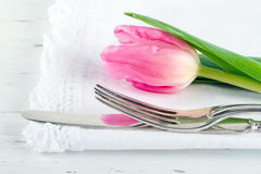 Closeup of pink tulip at rustic dinner setting Stock Photo