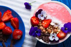 Closeup pink yogurt bowl with strawberry, nuts, chocolate, decorated with flowers, on striped light napkin, top view. Spring healthy breakfast, overhead view royalty free stock image