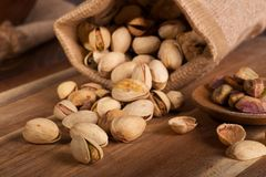 Pistachio Nuts Spilled From a Burlap Bag royalty free stock images