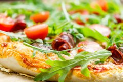 Closeup of pizza with parma ham and arugula Stock Image