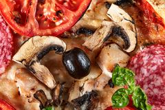 Closeup of pizza with salami, tomatoes and olives royalty free stock photos