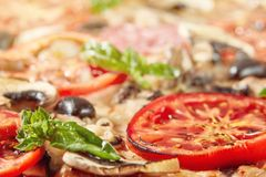 Closeup of pizza with salami, tomatoes and olives stock photo