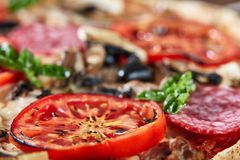 Closeup of pizza with salami, tomatoes and olives royalty free stock image